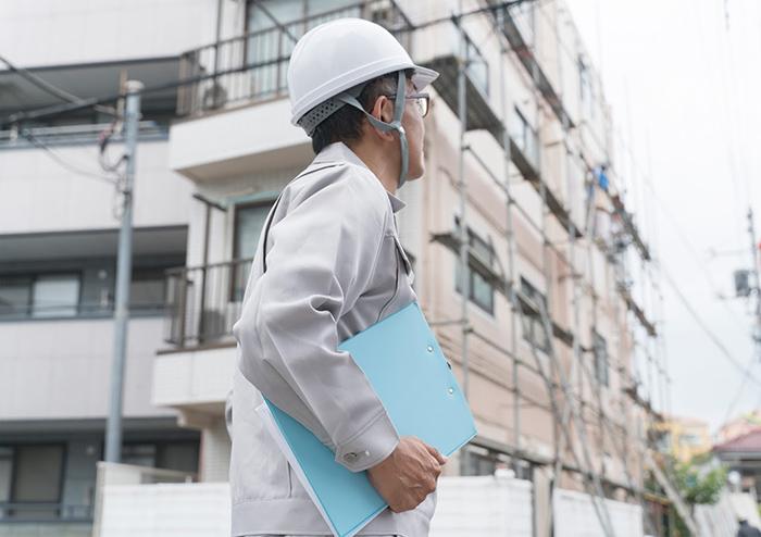 建物とヘルメットの男性